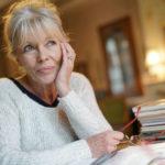 femme senior réfléchit livre